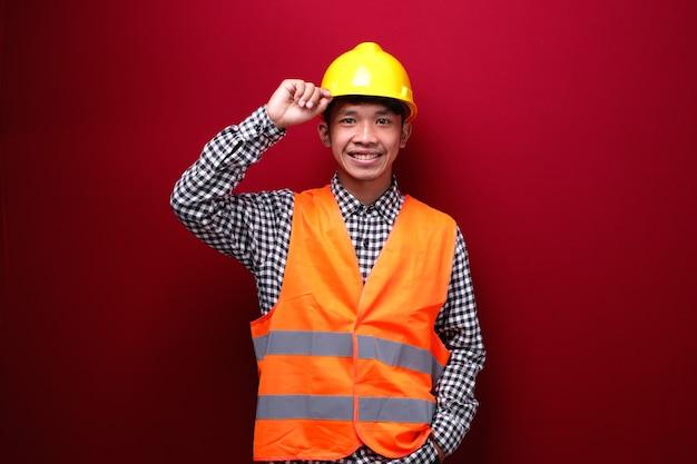 Homem asiático vestindo uniforme de contratado e capacete de segurança com expressão alegre