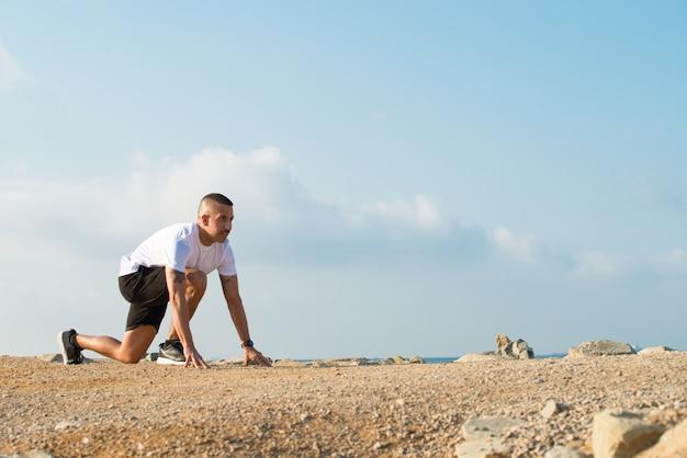 Homem aspirado na posição inicial antes da corrida