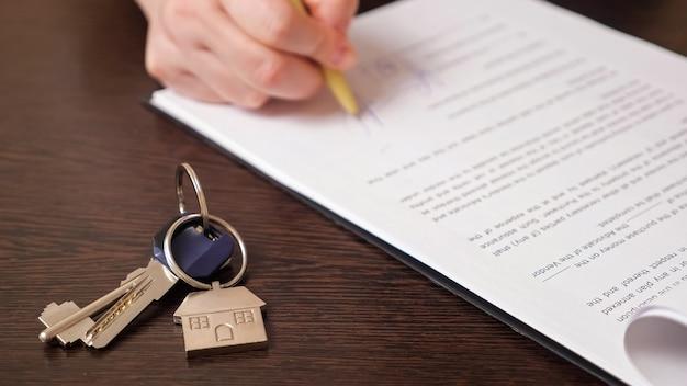 Homem assina contrato de compra de apartamento perto de chaves na mesa