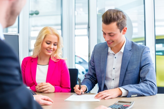 Homem, assinando, contrato vendas, para, automático, em, concessionária carro