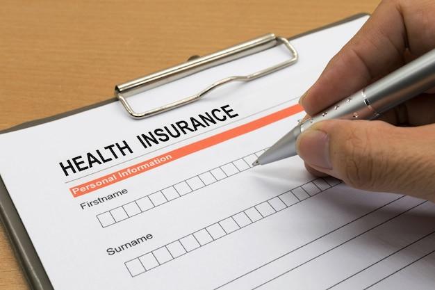 Homem, assinando, um, apólice de seguro saúde