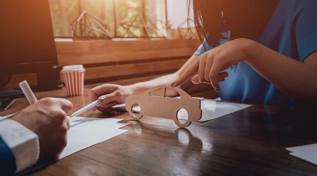 Homem assinando uma apólice de seguro de carro, o agente está segurando o modelo de carro de madeira.