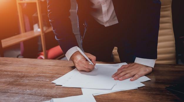 Homem assinar uma apólice de seguro de casa em empréstimos à habitação. agente imobiliário com o cliente antes da assinatura do contrato.