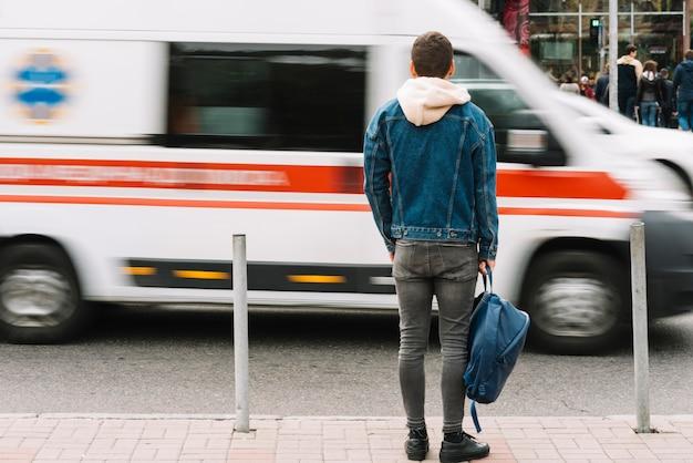 Homem assistindo ambulância passar