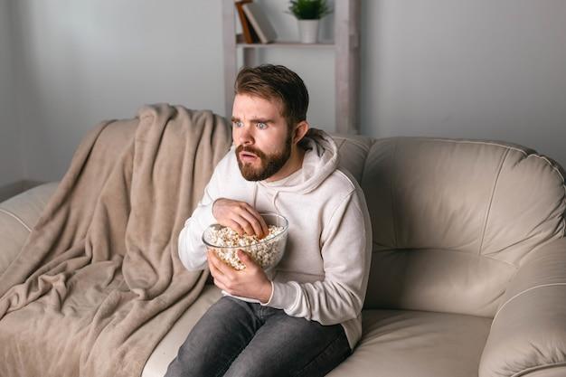 Homem assistindo filmes sentado em um sofá em casa
