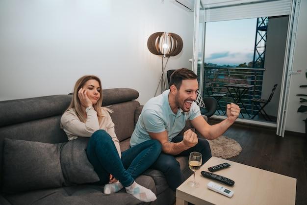 Homem assistindo futebol, enquanto sua namorada está sentada além dele entediado.