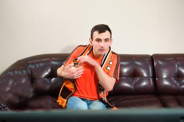 Homem assistindo futebol, fã de futebol, esportes em casa.
