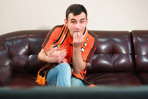 Homem assistindo futebol, fã de futebol no sofá.