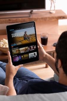 Homem assistindo netflix em seu tablet