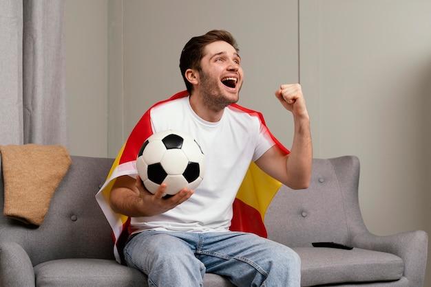 Homem assistindo programa de esporte na tv