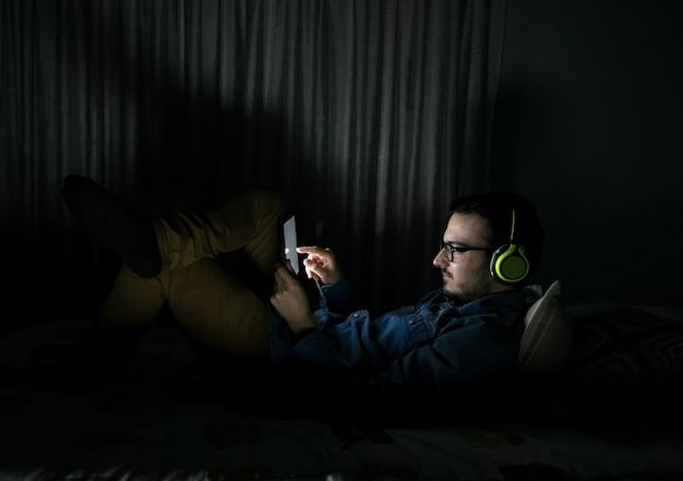 Homem assistindo séries de tv em um tablet sentado em uma cama no meio da noite em casa