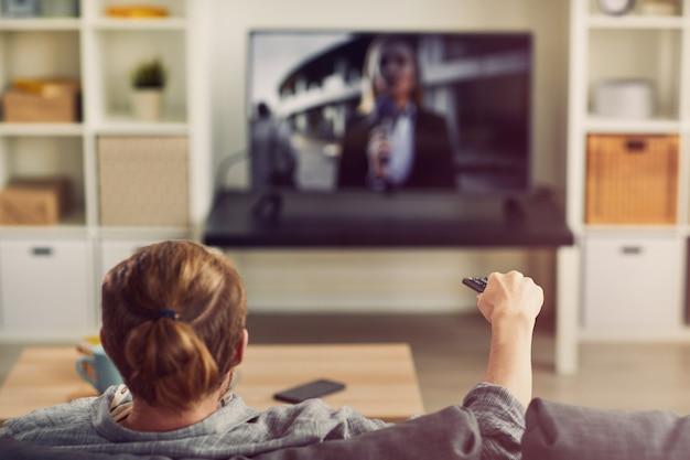 Homem assistindo tv de tela grande