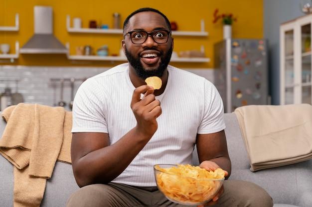 Homem assistindo tv e comendo batatinhas