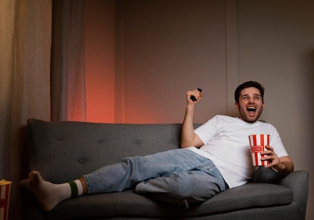 Homem assistindo tv e comendo pipoca