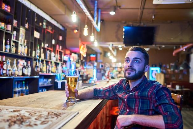 Homem assistindo tv no bar de cerveja