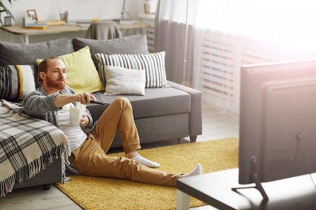 Homem assistindo tv no chão