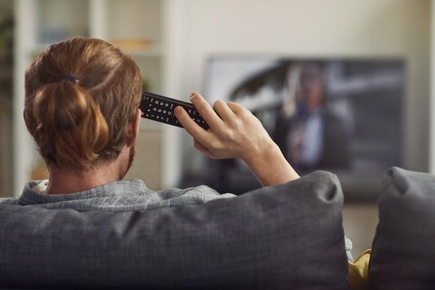Homem assistindo tv vista traseira