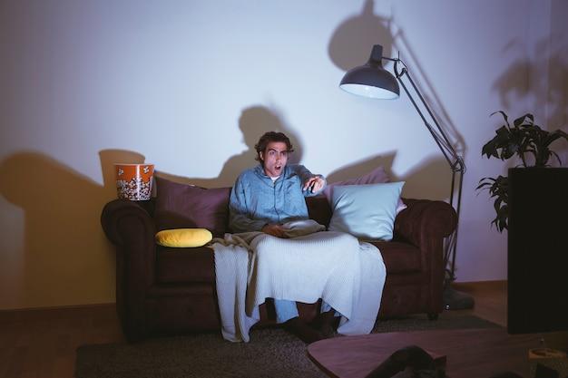 Homem assistindo um filme no sofá