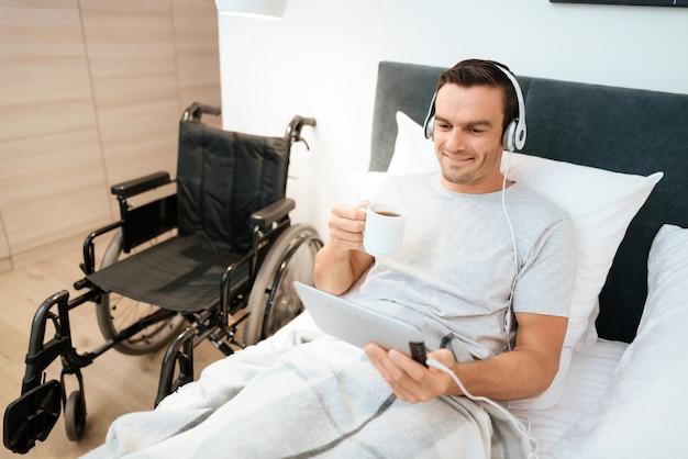Homem assistir vídeo no pad em fones de ouvido e segurar a taça.
