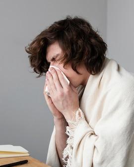 Homem assoando o nariz dentro de casa
