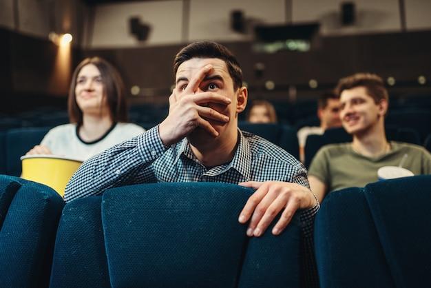 Homem assustado assistindo filme no cinema. showtime, entretenimento