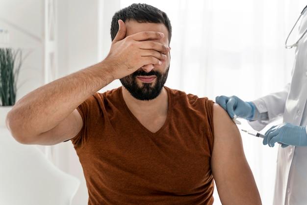Homem assustado cobrindo os olhos antes de ser vacinado