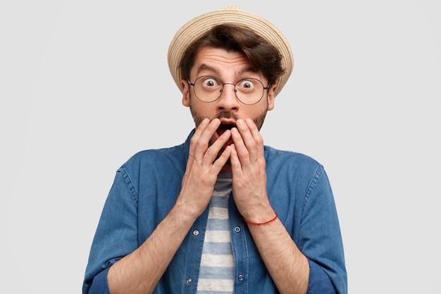 Homem assustado com a barba por fazer, cobre a boca com as duas mãos, vestido casualmente, não consegue acreditar nos olhos, vê algo surpreendente, isolado sobre uma parede branca