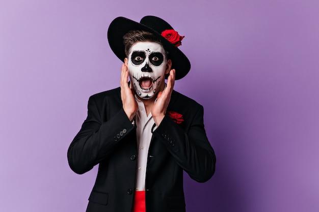 Homem assustado com chapéu de aba larga olhando horrorizado para a câmera. retrato do cara com maquiagem de halloween, posando em fundo roxo.