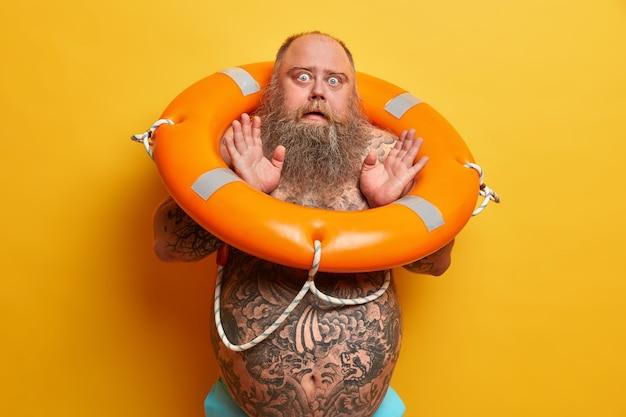 Homem assustado de olhos esbugalhados com barba espessa e corpo tatuado, medo de nadar, carrega uma bóia salva-vidas inflada, isolada na parede amarela. cara com excesso de peso passa o verão na praia. conceito de estilo de vida