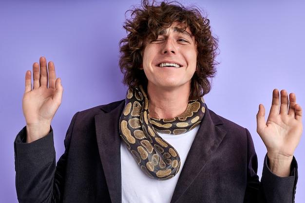 Homem assustado de terno com uma cobra exótica no pescoço, homem sofre de herpetofobia. retrato