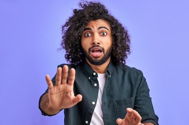 Homem assustado em pânico está gesticulando para parar, com medo de alguma coisa. jovem árabe com longos cabelos cacheados com medo e apavorado com a expressão de medo