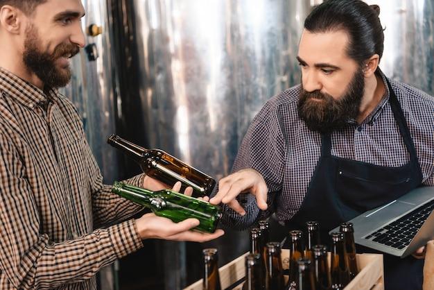 Homem atento que escolhe o microbrewery das garrafas de cerveja.