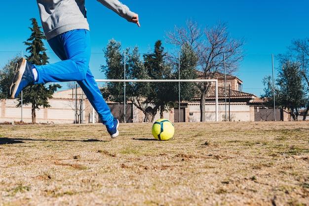 Homem atirando um tiro livre em direção ao gol. campo de futebol de campo.