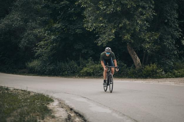 Homem ativo andando em bicicleta esportiva ao longo de trilha na floresta
