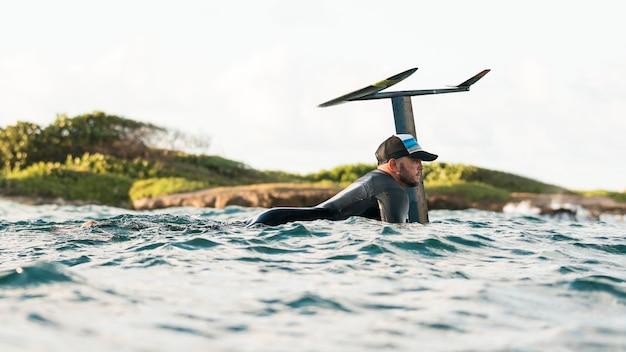 Homem ativo com equipamento especial permanecendo em uma prancha de surfe