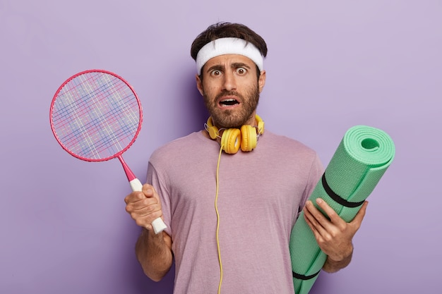 Homem ativo e indignado posando com equipamentos esportivos