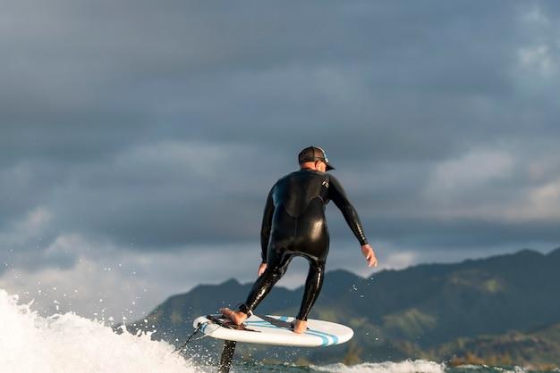 Homem ativo em equipamentos especiais surfando no havaí