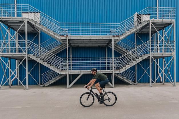 Homem ativo em roupas esportivas andando de bicicleta ao ar livre na parede azul