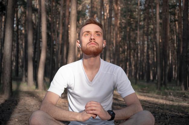 Homem ativo senta-se na floresta de pinheiros e gosta de meditar ao ar livre