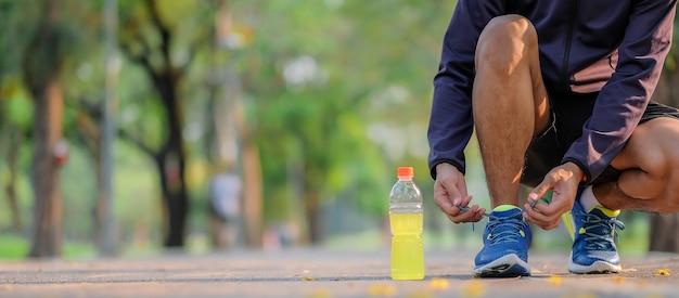 Homem atleta, amarrando os tênis no parque ao ar livre