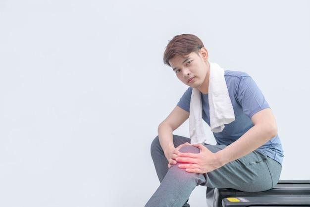 Homem atleta com dor no joelho depois de correr na esteira.