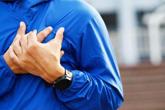 Homem atleta correndo correndo com dor no peito durante o exercício - ataque cardíaco ao ar livre. ou exercícios pesados fazem com que o corpo cause choque em doenças cardíacas. pode causar risco de vida. conceito de cuidados de saúde.