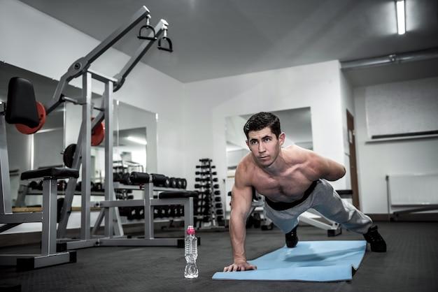 Homem atleta fazendo flexões na academia de esportes