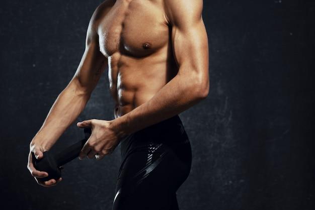 Homem atleta inflado corpo treino ginásio fundo escuro. foto de alta qualidade