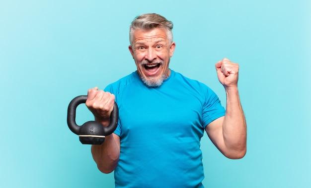 Homem atleta sênior se sentindo chocado, animado e feliz, rindo e comemorando o sucesso, dizendo uau!
