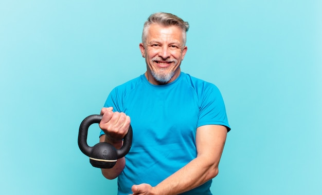 Homem atleta sênior sorrindo alegremente, sentindo-se feliz e mostrando um conceito no espaço da cópia com a palma da mão