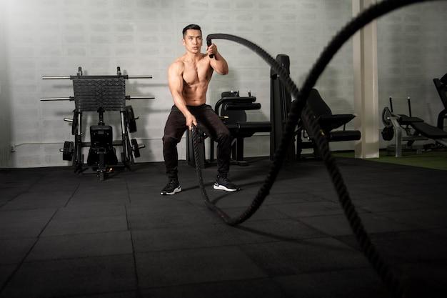 Homem atlético asiático com corda fazendo exercício no ginásio de fitness