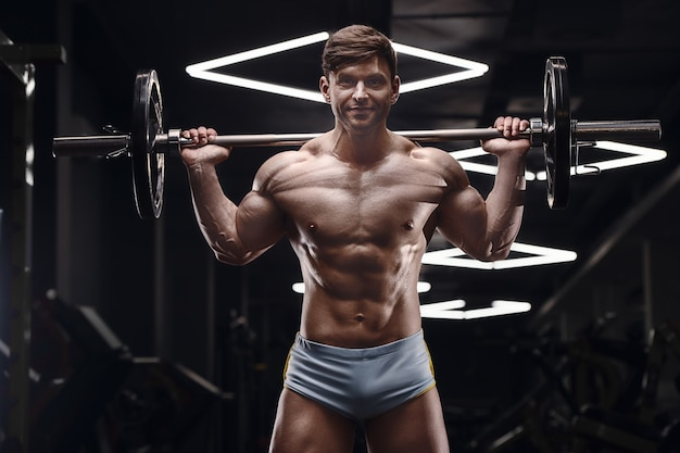 Homem atlético bombeando fazendo exercícios de estocadas no ginásio. aumentar os músculos das pernas com barra, fitness e conceito de esporte
