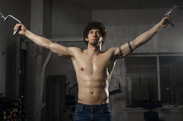 Homem atlético bonito treina seu peito no ginásio fitness masculino
