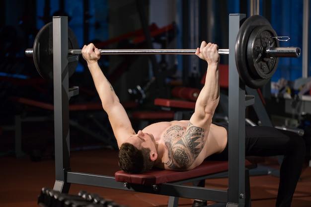 Homem atlético brutal bombeando músculos no supino